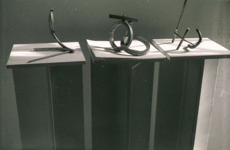 Three of Tam's iron sculptures on plinths. They are photographed with long shadows.