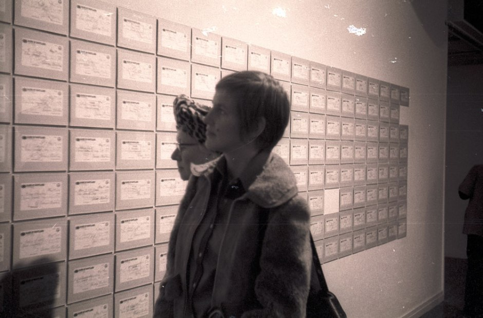 Gunnie with short hair standing infront of a wall of cheques.