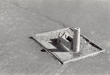 St Magnus Kirk on Egilsay photographed from the sky, a long shadow of the turret cuts across the kite shape creaed by the stone wall.