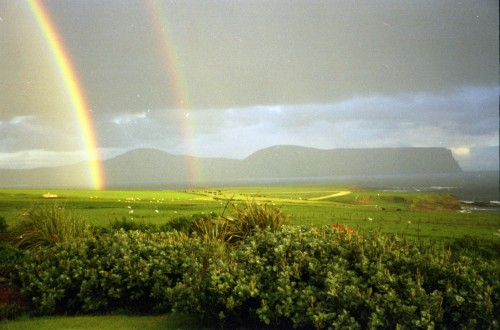 A double rainbow set against the blue hills of Hoy over the field in front of Don.