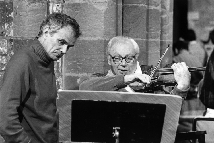 Peter Maxwell Davies looks at the sheet music on a lecturn being played by Isaac Stern on violin