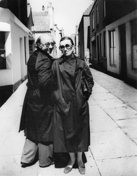 The artists Gennady Rozhdestvensky, Russian composer, and Viktoria Postnikova, Russian pianist, in dark raincoats, his back facing the camera and his head turned as he links arms with Viktoria who smiles eyes closed facing the camera hands in pockets.
