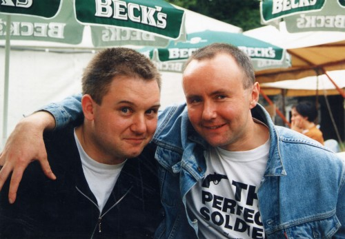 Writers Duncan McLean and Irvine Welsh arms round shoulders smiling at the camera