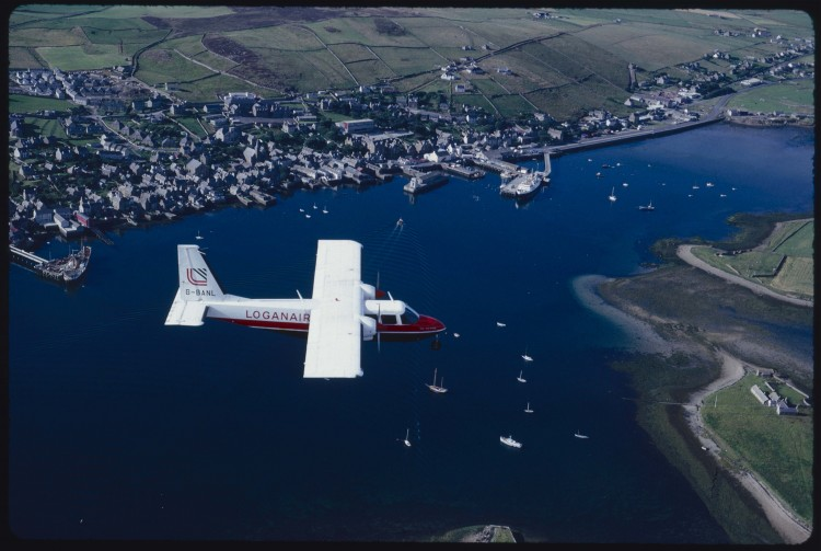 looking down on a small Logan Air plane as it flies over Stromness Harbour