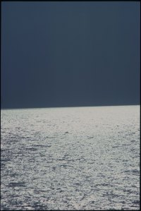 dark sky cut across by  abright shimmer sea
