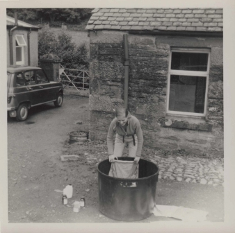 Gunnie making batik in bucket outside, image shows courtyard and Gunnie hunched over a large tub pulling cloth out.