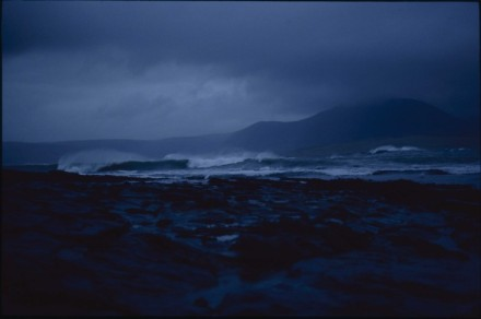 A dark deep blue scene of crashing waves, black rocks and the hills of Hoy rising from the mist.