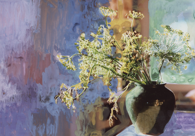 A black pot holds an arrangement of wild flowers, they sit on a table in the far right of the photograph. All around the background has been painted out in patches of blues and warm mauves