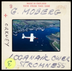 slide mount with handwritten title and artists name G. Moberg. Image is the Loganair plane over Stromness.