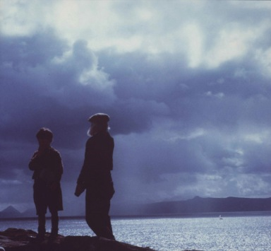 An old man and a young boy are silhoutted against a broody sky and shimmering sea