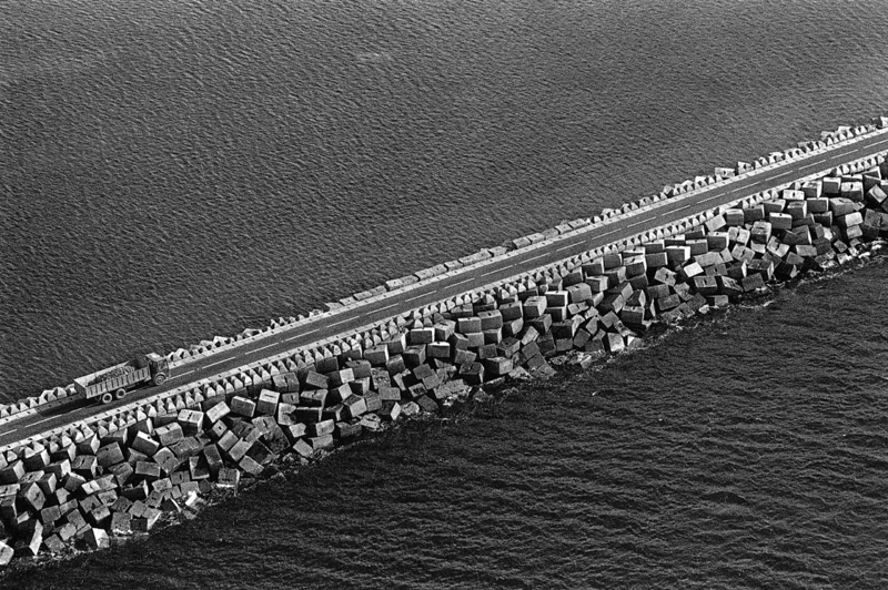A road shored up with concrete blocks cuts diagonally across the frame, either side is a dark tone of sea. On this causeway a trck appears in the bottom left of the frame. The most noticeable part of the trcuk is the circles of the wheels, their roundness contrasting with the sharp edges of the blocks. The dark shadowy sides of the blocks meet bright sunlit sides, their strong shapes set against the soft texture of a dark sea.