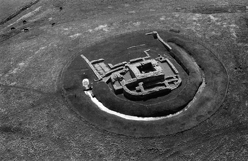 This black and white aerial photograph of the remaining ground floor of a former stronghold, shows the surrounding ditch encircling the curved walls and a dominant black square of a cellar and well central to the site. From above the archaeological site is a sketch in stone.