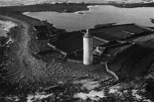 An aerial view of the north end of North Ronaldsay. The Old Beacon 18th century lighthouse sits sunlit just off centre of the photograph. All around the foot of the lighthouse stone enclosures, punds for sheep, etch themselves along the shoreline. Beyond a loch and the sea on the horizon.