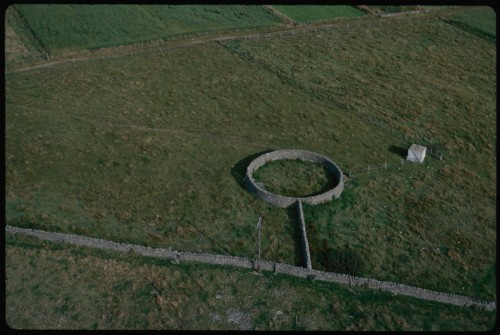 This aerial colour photograph is of a stone wall with an additional wall jutting off ending in a small circular enclosure.