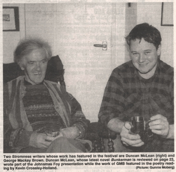 Two authors, one older one younger sit together each nursing a cup of ale.