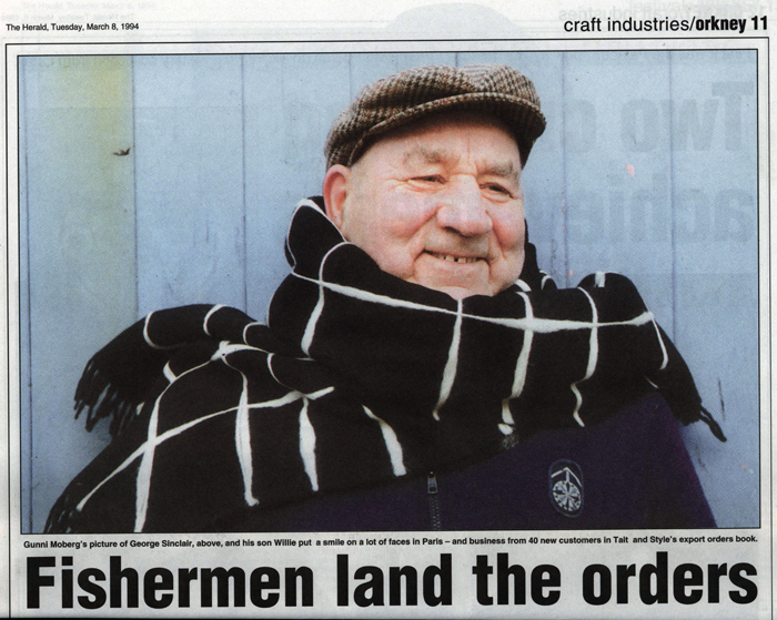 A fisherman in cap and warm smiling face is swaddled in a huge black and hwite scarf wrapped round his neck.