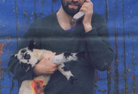 a farmer inforont of a peeling blue door with a lamb in one arm and a large phone with an aerial in the other, he wears shades and is bearded, the lamb has been dabbed with bright yellow iodine.