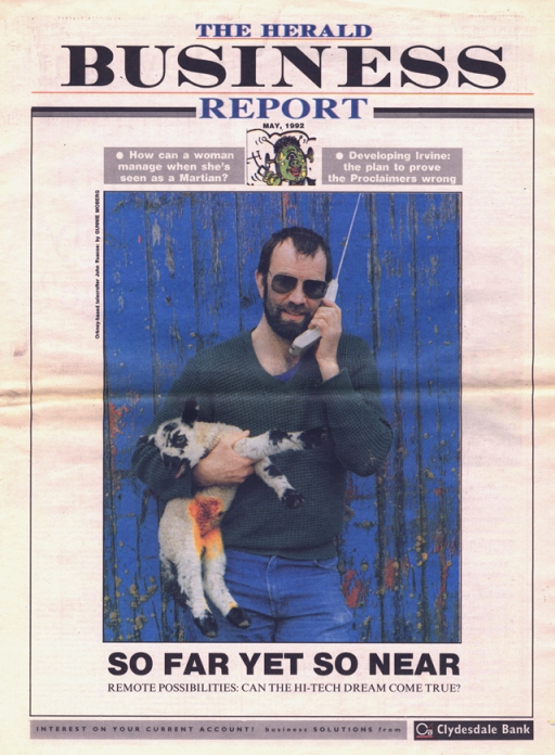 the cover of the Herald Business report newspaper section, image on cover of a farmer inforont of a peeling blue door with a lamb in one arm and a large phone with an aerial in the other, he wears shades and is bearded, the lamb has been dabbed with bright yellow iodine.