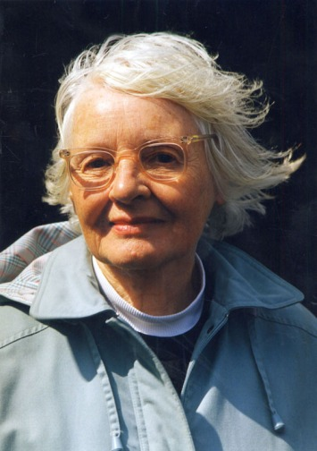 Poet and filmmaker Margaret Tait stares direct to camera, her white hair blown from her strong features. A white collared jumper looks at first like a dog collar. Strong light creates a glow from her white hair against the blcak shadowed background.