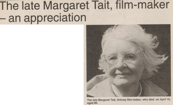 The photograph in the newspapper clipping is of an older woman looking directly into the lens with clear rimmed winged glasses and her white hair blowing in the wind glows against the black background.