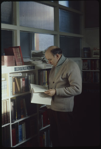 A man in a light blue polo neck and camel cardigan browses a book beside the reference section of Stromness Library.