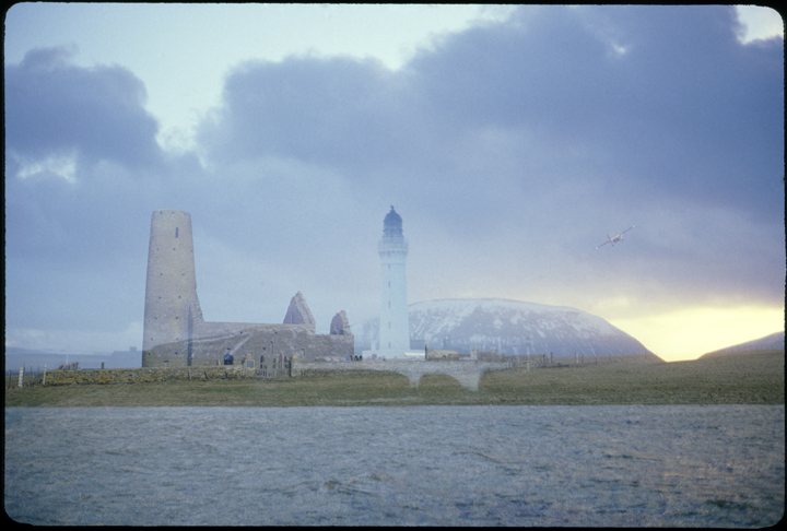 On the left of the image stands a church with a high tower beside it in an unlikely pairing is the white tower of a lighthouse. Behind them rises a blue snow dusted hill and on the right a small red plane flies in the blue clouds. Sea balances the blue of the sky.