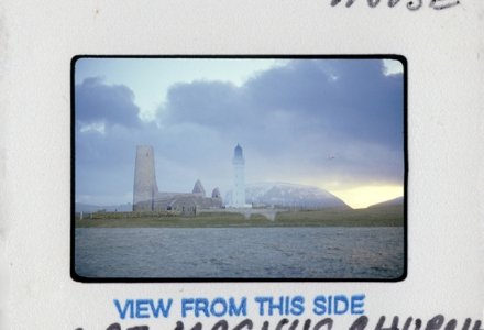 Slide and mount, writing reads Hoy High Lighthouse on top of slide and at the bottom, St. Magnus Church Egilsay. There in the picture are both places, blended in a double exposure.