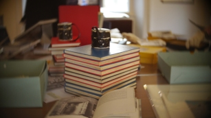 Diaries from the Gunnie Moberg Archive with one of Gunnie's lenses sitting on top of them with print boxes and books on the table.
