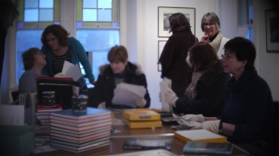 A group of people discuss prints from the archive