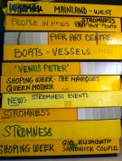 A stack of ten yello print boxes labelled with Gunnie's distinctive generous writing..'boats, piers, Stromness news, Pier Arts Centre..'