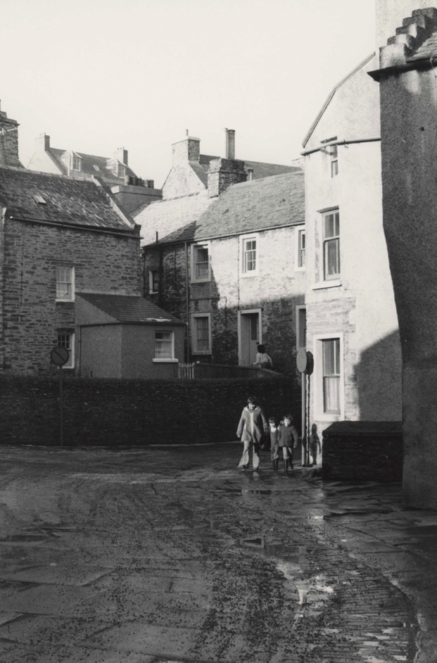 Black and white street scene of Stromness, a family turn the bend at the bottom of Hellihole road