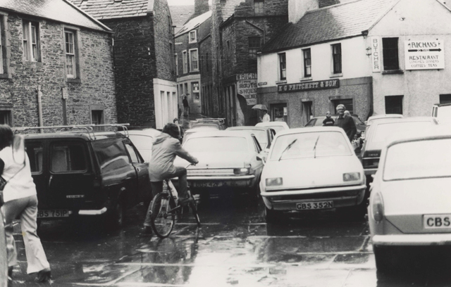 Black and white photograph of Graham Place Stromness packed across with cars in both directions and a man on a bike waiting, among the cars an amused Archie Bevan spots Gunnie Moberg taking the photograph and smiles