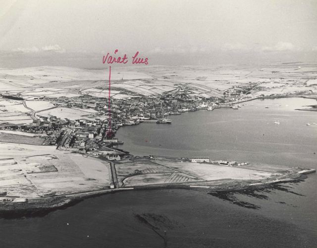 Aerial black and white of Stromness covered in a light dusting of snow. In red pen written in Gunnie's hand 'varat hus' with a big arrow pointing down to 'our house'