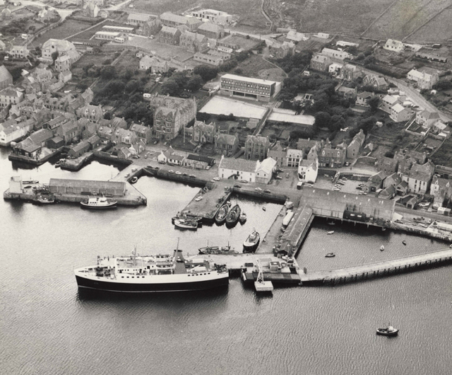 Aerial black and white photograph of Stromness showing the pier lined waterfront and the ferry tied up at the pier