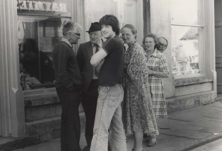 A group of people gather in a Stromness Street to catch up. A young man in flares turns to look at the camera and an older man peeks from behind his wife to smile