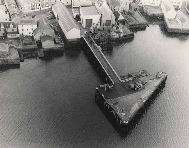 Black and white aerial photograph showing Stromness waterfront and pointing out into the sea, the arrow head shape of the Pole Star pier