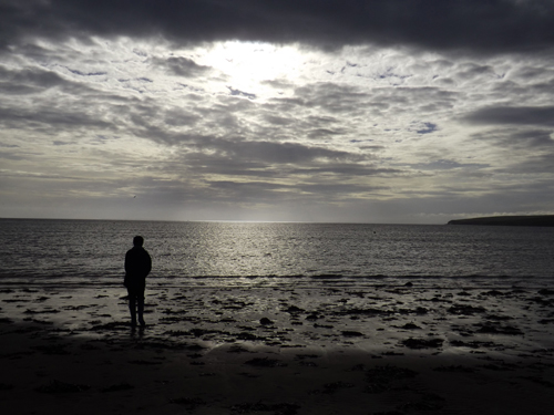 A woman in sihlouette stands on the shore.