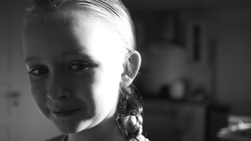 A young girl smiles from the far left of this black & white photograph, her face in shadow while a strong window light picks up her hair and moulds the side of her face.