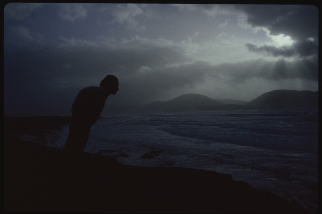 A man leans forward held up by the wind, his jacket fills with wind and his shape echoes the Hoy hills behind. The image is dark and storm clouds gather.