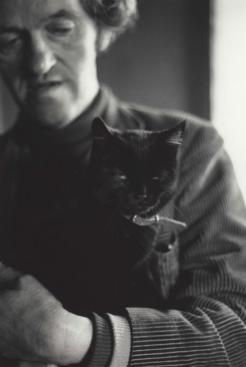 George Mackay Brown in the background out of focus curls an arm around his cat who looks sharp in to the lens.