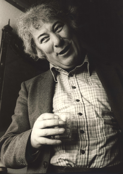 Seamus Heaney in mid conversation, animated, head to one side, mouth and eyes smiling, drink in hand.