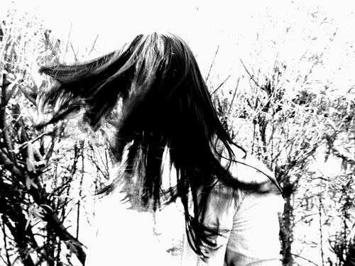 Hair totally obscures the face in this black and white photograph of a woman caught in the action of shaking her head.