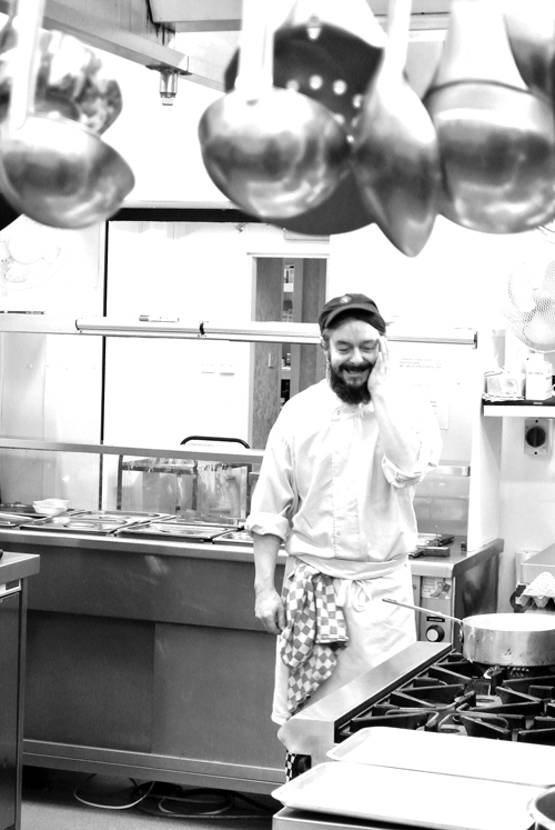 A chef stands in a kitchen smiling with hand raised to his head, above him ladels and spoons hang shiny and metallic in this black and white photograph.