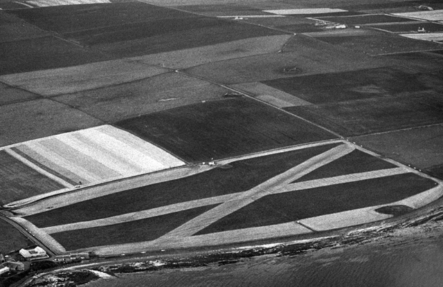 aerial image in black and white of a landscape of fields beside the sea, one field catches the eye, it has been harvested in a cross, the effect is suggestive of a giant st andrews flag
