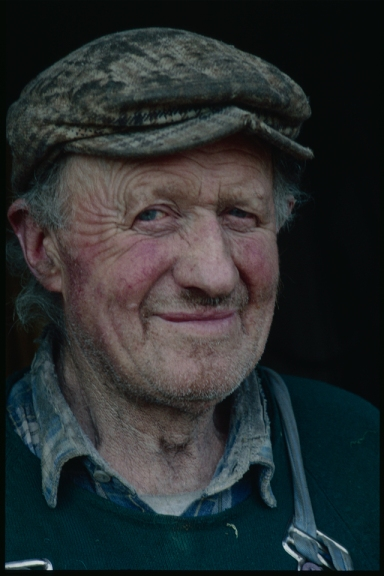 A kind faced farmer smiles at the camera, the smile wrinkles at hios eyes. Oiled and worn cap and frayed shirt collar- comfortable working clothes, familiar.
