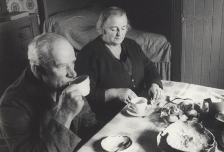 A man and woman sit in light from the window at the table of tea cups and baking. Behind them a box bed. The photograph is blacka nd white and taken from a high position, perhaps Gunnie was standing on a chair.