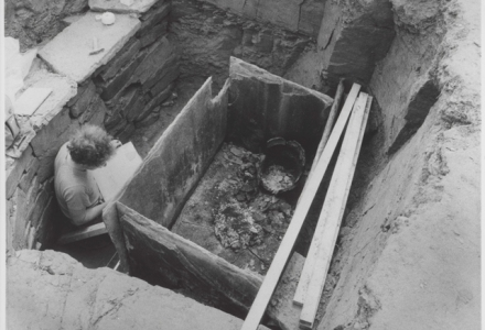 An archaeologist peers into a stone box with an open urn in one corner, the pit he stands in is above his shouldre height and is lined with stonework. Across the cist lie planks leading you into the photograph.