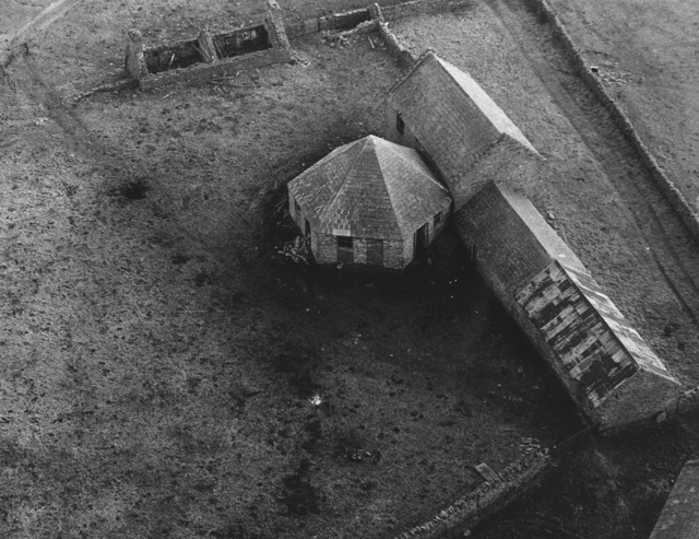 Black and white aerial photograph of farm buildings, an intriguing hexagonal roofed buidling draws the attention.