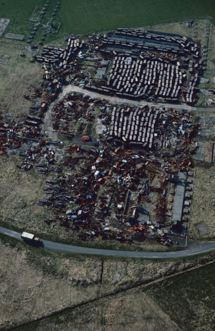 Aerial photograph showing a mosaic of refuse at a dump, curving round the bootiom of the frame is a road with a lorry on it.
