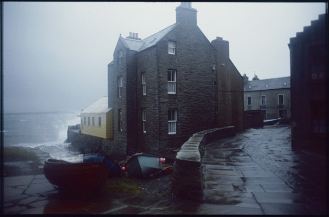 Stromness on a wet day, waves the yellow boatshed of a tall house. Boats drawn up give some colour in the greyness.